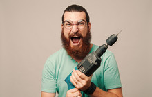 Young Man With Beard Screaming Holding A Drill In Hands.