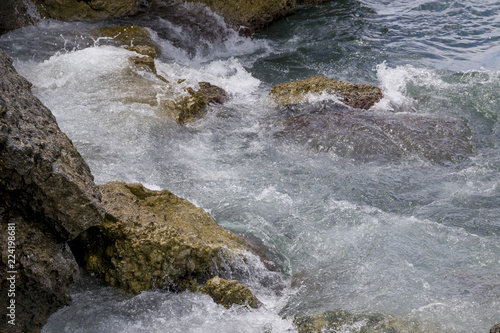 Tuinposter Kust Coast stones with white spray on Corfu / Greece