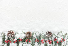 Snow Covered Christmas Background With Fir Twigs, Pine Cones And Berries