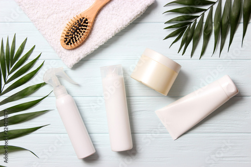 Fotografia natural hair care products, hairbrush, towel and leaves on a wooden background top view