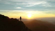 The Male Standing On The Mountain And Enjoying The Beautiful Sunset