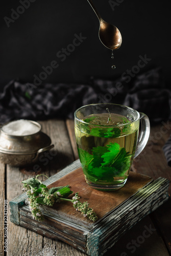Staande foto Thee A cup of hot herbal tea made from lemon balm on a wooden background. Melissa branches, sugar bowl, backlight. Country house evening relax concept.