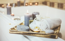 Candles And Spa Essentials On Wooden Tray In Bathroom, Essential Oil, Bath Salt On Wooden Spoon, Pumice Stone, Towel, Sea Stone, White Orchids. Spa Products Set Conception. Instagram Filter Style.