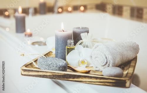 Candles and spa essentials on wooden tray in bathroom, essential oil, bath salt on wooden spoon, pumice stone, towel, sea stone, white orchids Fototapete