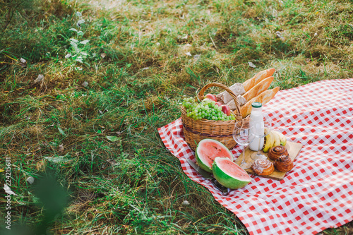 Healthy food for picnic outside. Closeup view of fresh buns, bread, yogurt, bananas, watermelon, green grape and red apples. Horizontal color image.