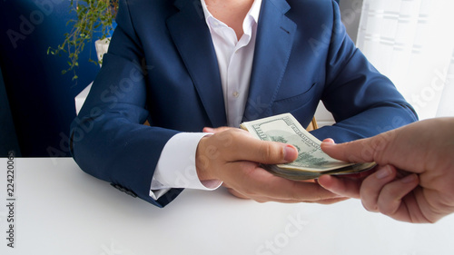 Fototapeta Closeup photo of businessman taking stack of money as bribe obraz