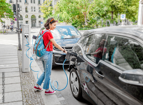 Fotomural Woman charging her electro car at special parking, alternative energy and eco co