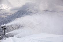 Snow Gun On The Background Of The Caucasus Mountains That Shoot Artificial Snow