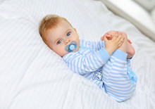 Charming Blue-eyed Baby 7 Month Old Lies In Bed In A Striped Bodysuit And Sucks A Pacifier