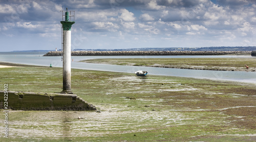 Foto op Aluminium Vuurtoren Low tide landscape with lighthouse an d small boat in St Brieuc, Brittany, France