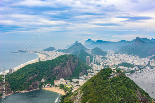 View of city Rio de Janeiro with Favelas in the hills with misty statue on mountain
