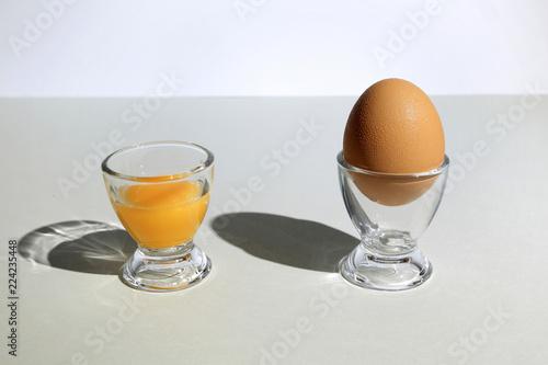 Obraz Żółtko z jaja kurzego w kieliszku i pusty kielich na szarym tle. - fototapety do salonu
