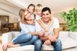 Leinwandbild Motiv Young  family at home smiling at camera