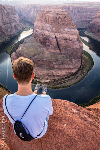 Keuken foto achterwand Verenigde Staten Mann sitzt am Horseshoe Bend mit Ausblick auf den Grand Canyon
