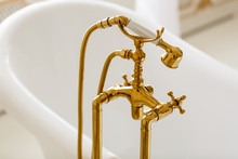 Rich Gold Faucet And White Bath In The Bathroom