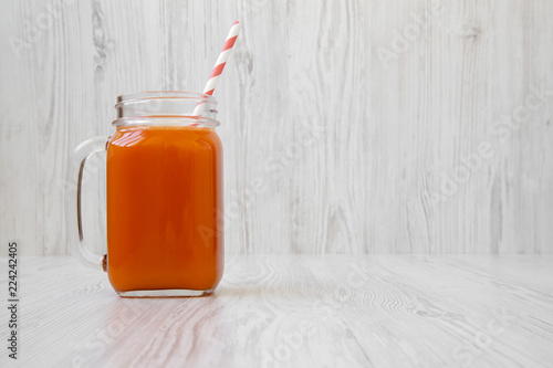 Fotografie, Obraz  Glass jar of carrot smoothie on white wooden background, side view