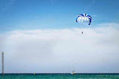 Water sport, active sport. Blue parachute hovers above the Mediterranean Sea. Parasailing also known as parascending or parakiting.