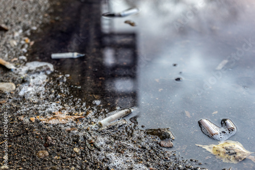 Fotografia, Obraz  cigarette butts and leaves in autumn puddle. selective focus