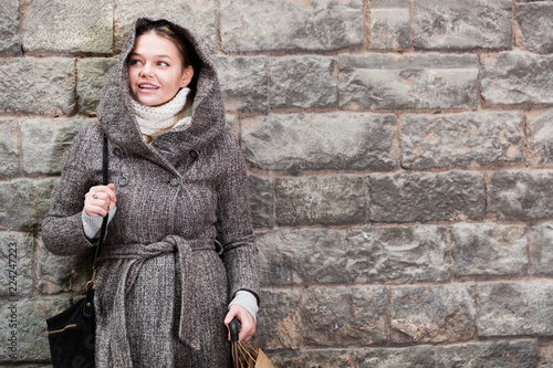 Fotografía  cheerful female in coat hood near wall