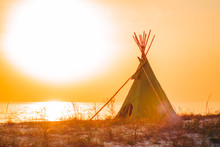 Wigwam On A Sandy Seashore. American Native Indian Building Outdoors In Summer. Teepee On A Sundown, In Warm Sunlight Against The Sea