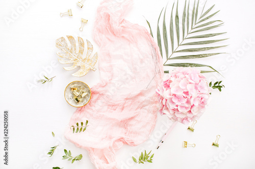 Foto auf AluDibond Hortensie Stylish composition with pink hydrangea flowers bouquet, tropical palm leaf, pastel blanket, monstera leaf plate and accessories on white background. Flat lay, top view rose gold desk.