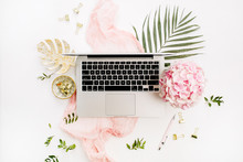 Modern Home Office Desk Workspace With Laptop, Pink Hydrangea Flowers Bouquet, Tropical Palm Leaf, Pastel Pink Blanket, Monstera Leaf Plate And Accessories On White Background. Flat Lay, Top View.