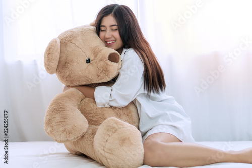 Attractive smiling happy young woman hugging her big teddy bear sitting on white bed at home. Lovely girl cheerful cuddle brown teddy bear at bedroom.