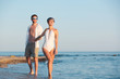Happy young couple walking together on beach. Space for text