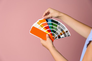 Female interior designer with palette samples on color background, closeup. Space for text