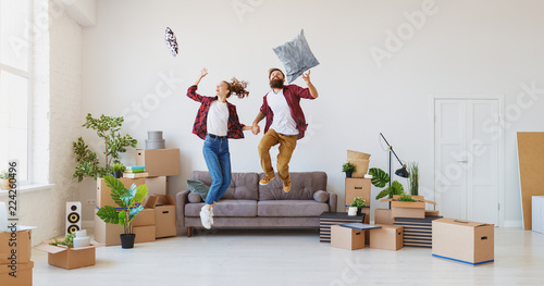 Obraz happy young married couple moves to new apartment and laughing,  jump, fight pillows - fototapety do salonu