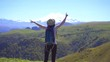 Young tourist girl with backpack gesturing success on the mountain, winner concept,slow mo
