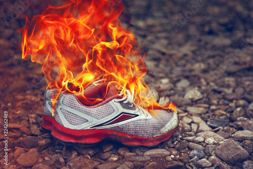 Foto op Canvas Kruiderij Burning Old Sneakers Or Shoes On Stone Surface Or Pebble Beach. Concept Of Passing Youth Or End Of Sports Career. Completion Of Tourist Trip Or Vacation. Pollution Of Nature With Fast Fading Things.