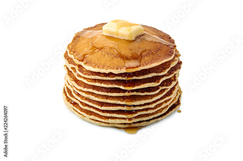 Stack of pancakes with butter and maple syrup on white