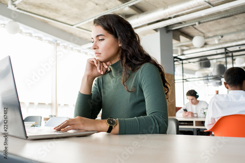 Fotografía Portrait of pensive young woman using laptop while working in open office, copy