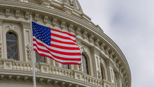 United States Capital Building With Waving American Flag In Washington DC With Light Blue Sky