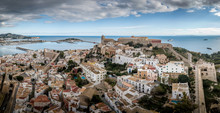 Aerial Panorama Of Ibiza Town With Fortifications, Bastions, Walls, Churches, White Houses Against Blue Stormy Cloudy Sky