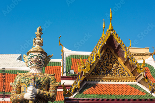 Tuinposter Bangkok Warrior statue with decorated roof on the background