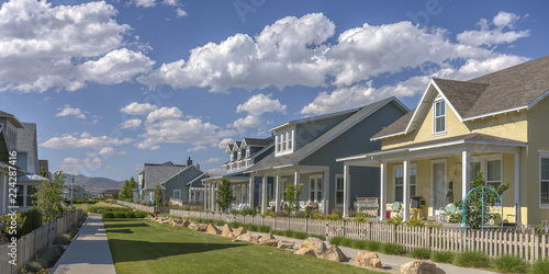Row of houses under blue sky and puffy clouds Wallpaper Mural