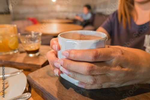 Poster de jardin Bar Female hand holding white cup of coffee ,in coffee shop.