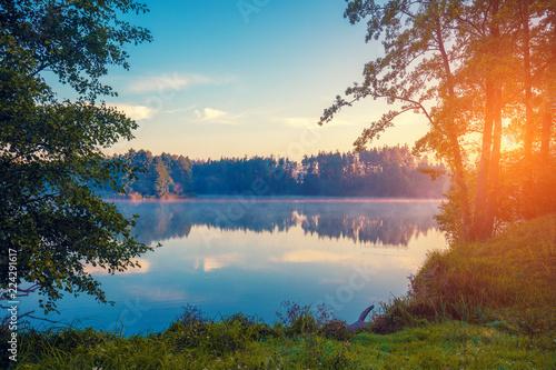 Plakat Wczesny poranek, wschód słońca nad jeziorem. Wiejski krajobraz, bezdroża. Piękna przyroda Finlandii, Europy