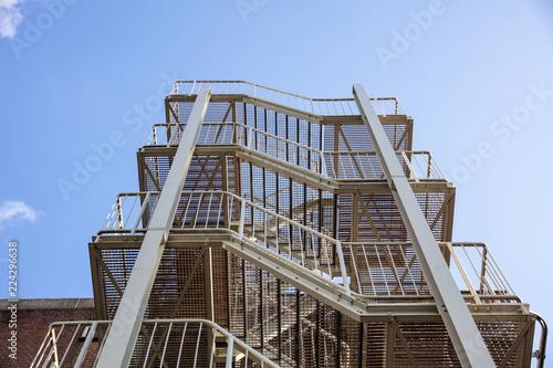 Carta da parati Fire escape. Building external steel staircase against a blue sky