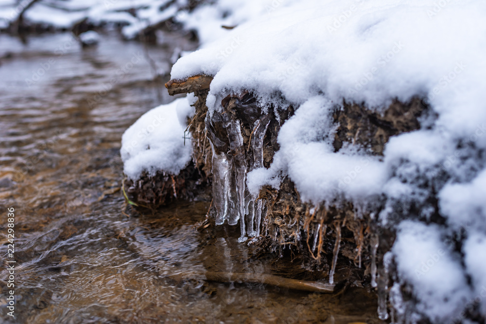 Fototapeta shore of the winter creek with snow and ice close up