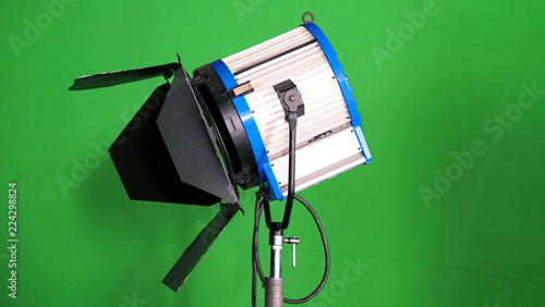 Valokuva  Big studio LED spotlight for video movie or photo film production with green screen background for chroma key technique in post lab process and professional equipment such as tripod and others