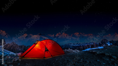Photo Night bivouac in Mountains, milion star hotel under night sky, red illuminated tent on pass in Alps
