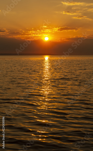 Golden Sunset into the sea with the silhouette of an island.