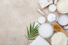 Spa Setting From Body Care, Wellness And Beauty Treatment. Organic Coconut Scrub, Oil And Cream On Stone Table Top View. Flat Lay.