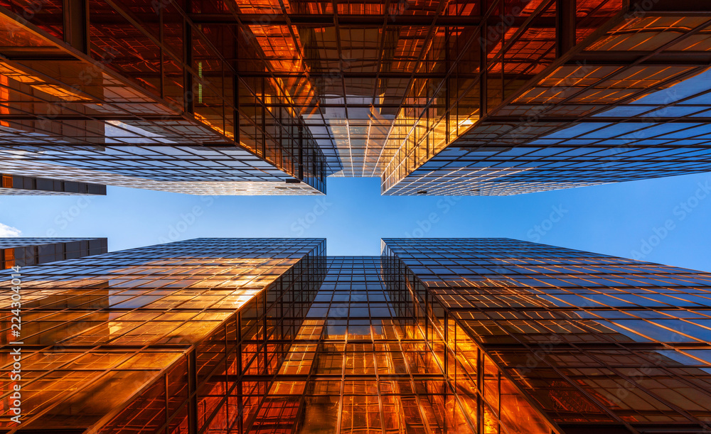 Fototapeta Golden building with blue sky. Windows glass of modern office skyscrapers. facade design. Architecture exterior for cityscape background.