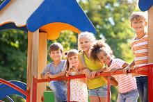 Cute Little Children Having Fun On Playground Outdoors