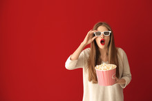 Emotional Young Woman With Cup Of Popcorn And 3D Cinema Glasses On Color Background