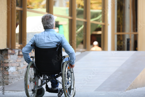 Senior man in wheelchair near ramp outdoors Canvas